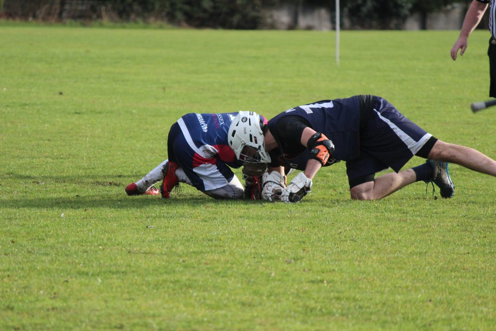 Nicoll fighting for possesion at face off against Sussex. Credit: Shani Kotecha
