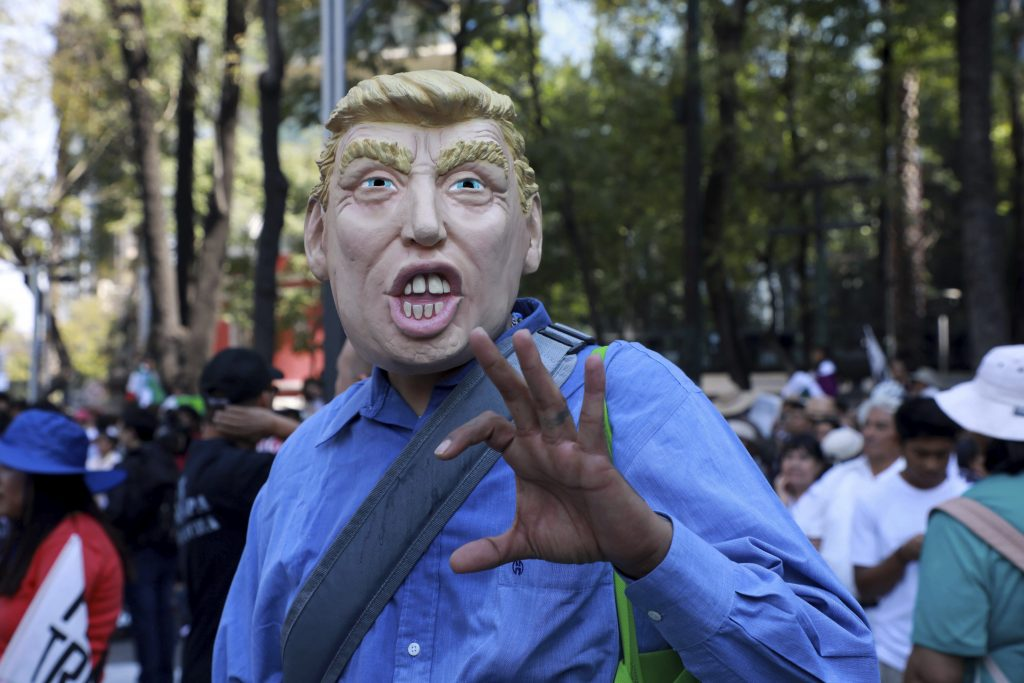 A protester in Mexico City wearing a Trump mask. Photo Credit: Rex Features