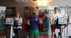 KU rugby players Lauren Haighton and Freddie Greef competing in the Bike-A-Thon with Spoony the mascot standing in the middle. Photo Credit: Michael Lloyd