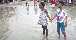 Girls hold hands as they help each other wade through floods after Hurricane Matthew in Les Cayes, Haiti. Photo Credit: Rex Features