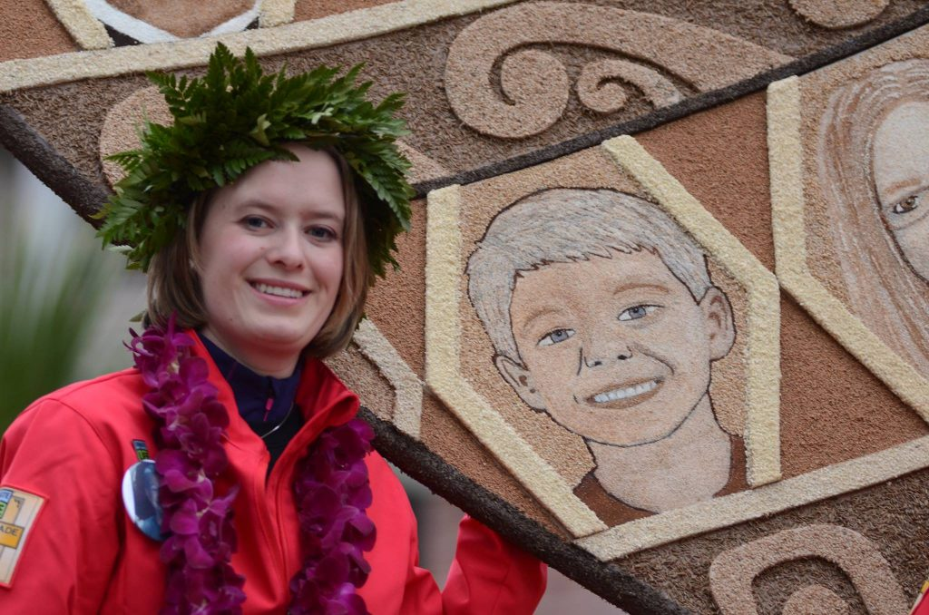 Katy Portell standing with the mosaic of her donor, PJ, on the Donate Life float at the Rose Bowl Parade. Photo Credit: Katy Portell Facebook