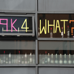 Student decorates door window with the words '9K for what?'