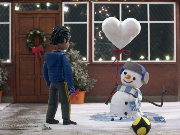 A snowman passes a balloon in the shape of a love heart to a child