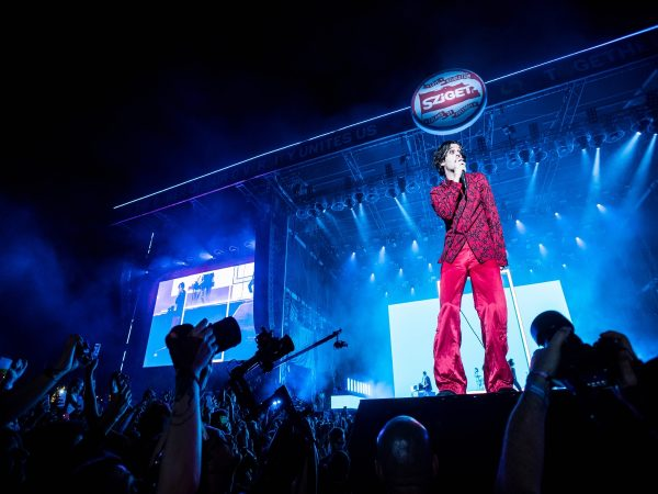 Matty Healy from The 1975 wearing an all-red suit during his performance in Budapest