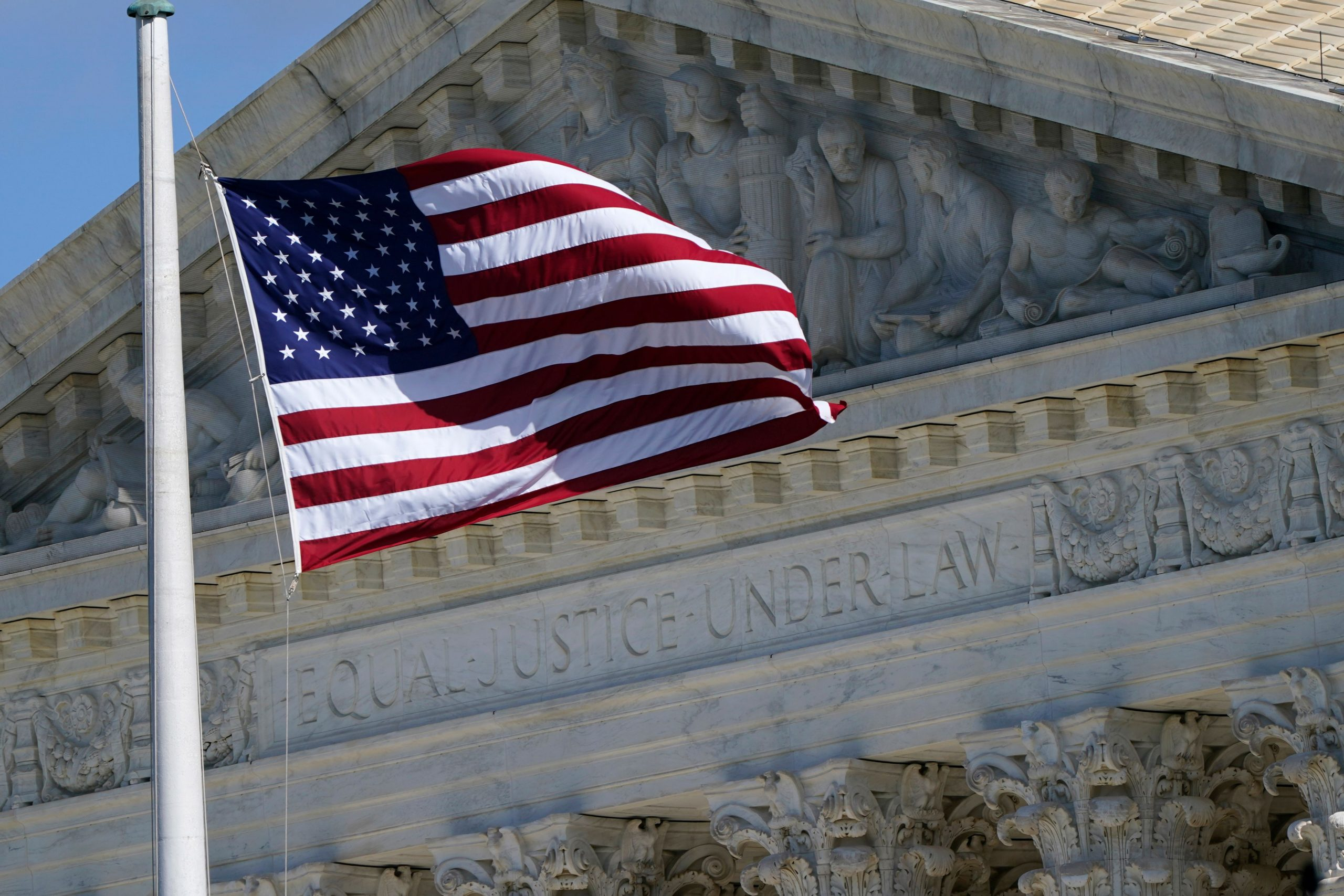 The US Flag is seen as the nations colours of red, white, and blue. With 50 white stars on the blue and 13 red and white stripes that is standing in front of the Supreme Court.