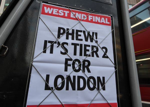 A headline on a wall in London that says 'PHEW! IT'S TIER 2 FOR LONDON'.