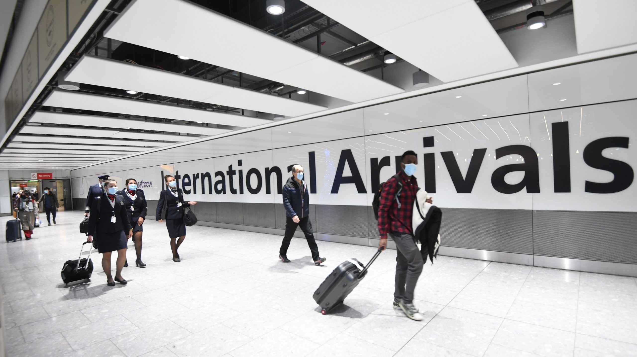 Passengers walking into arrivals at Heathrow airport.