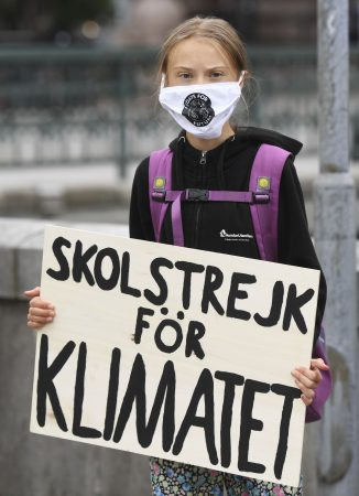 Greta Thunberg holding a sign which reads: School strike for climate.