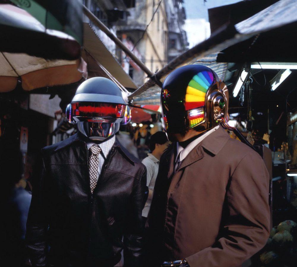 Two men in robot helmets standing in a mid shot.