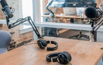 Podcast mics and headphones on a table.