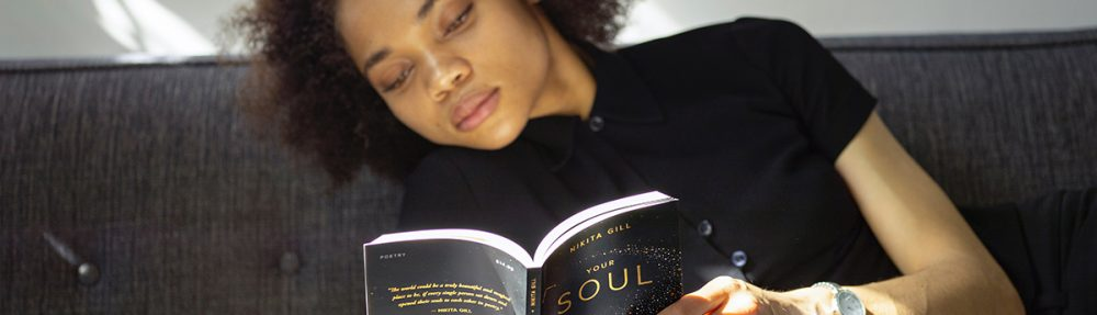 Person laying on couch reading a book.