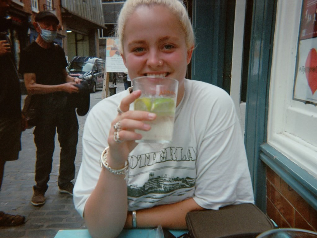 Reid is sitting down, holding a glass up to her mouth. She is wearing rings, has bleached hair and is smiling.