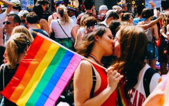 Two people kissing at a Pride parade in London. One of them is holding a rainbow flag.