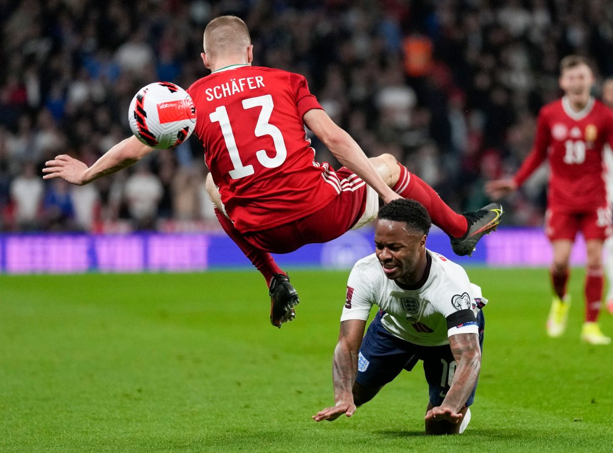 Hungary's Andras Schafer, top, collides with England's Raheem Sterling as they compete for the ball during the World Cup 2022 group I qualifying soccer match between England and Hungary at Wembley stadium in London