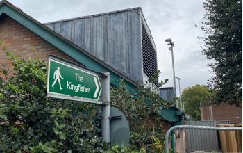 Green signpost which reads 'The Kingfisher' outside Leisure Centre