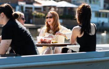 Two people sitting by a table enjoying a meal and the sunshine.